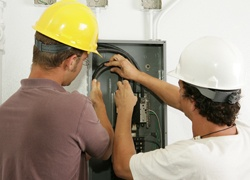 Electricians working together to install a breaker panel. Models are actual electricians - all work is performed according to industry standard code and safety practices.